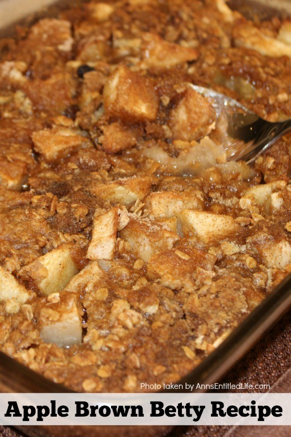 Close-up photo of a 13x9 pan filled with an apple brown betty dessert, a spoon in the center of the pan starting to lift a taste of the dessert