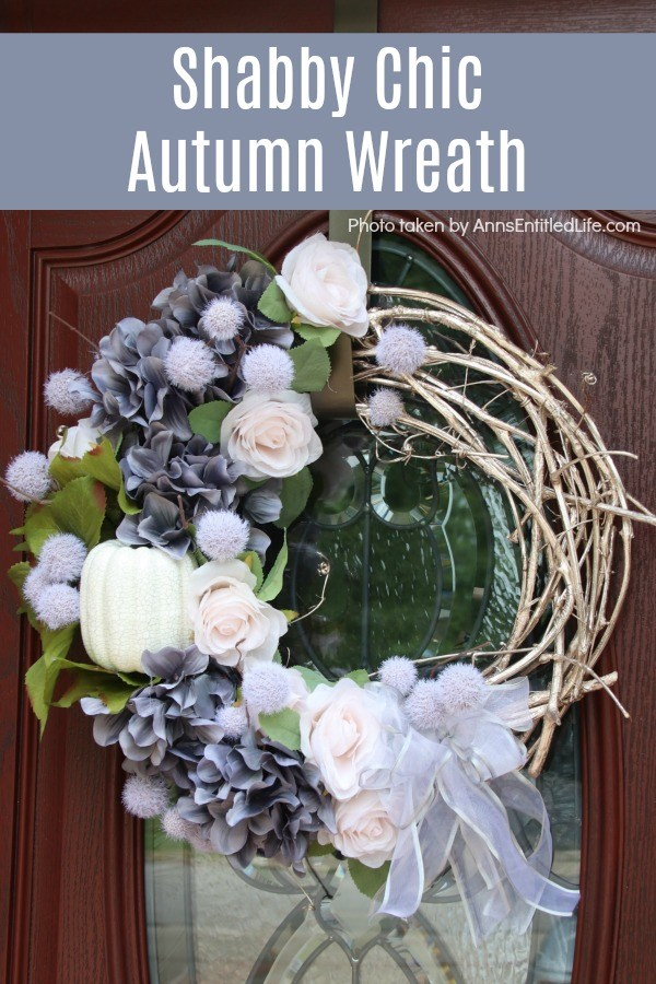 A beautiful fall wreath in colors of grey, blush, and white on a grapevine wreath, hanging on a brown door with a glass insert