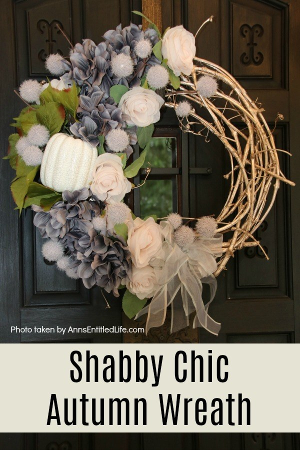 A beautiful fall wreath in colors of grey, blush, and white on a grapevine wreath, hanging on gold wreath hanger against a black door with a glass insert