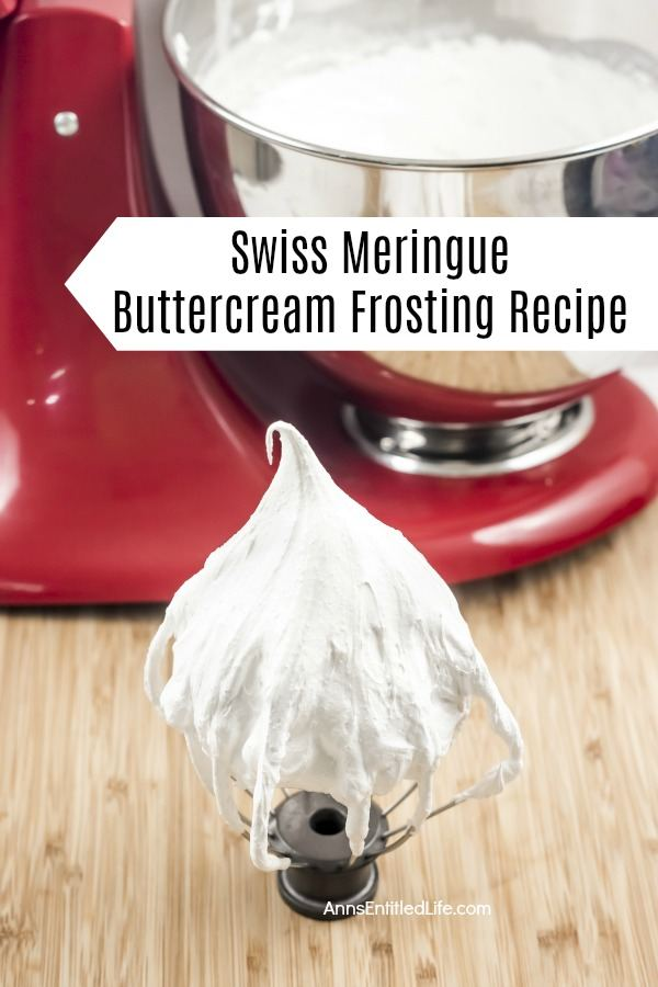 A standing whisk beater is in the front and center with white Swiss meringue buttercream frosting adhered to it. There is a red stand mixer in the background with the remainder of the frosting inside of it. This is on a wooden board.