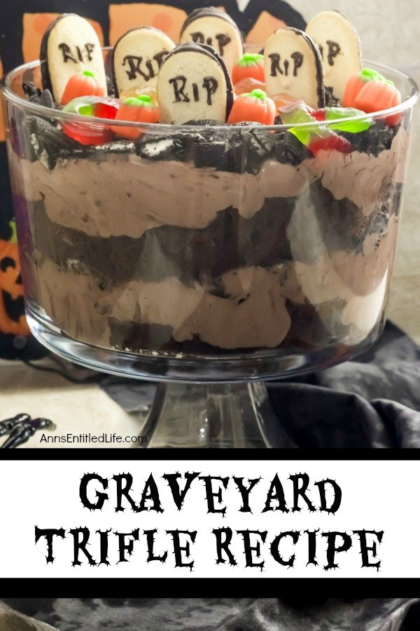 A front-facing view of a layered chocolate trifle with a graveyard setting at the top (grave markers, pumpkins, gummy spiders, and crushed Oreos) in a clear trifle bowl, on top of a black and white table covering. A bone hand is on the left of the trifle bowl.