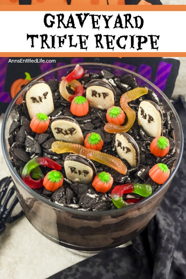 An overhead view of a layered chocolate trifle with a graveyard setting at the top (grave markers, pumpkins, gummy spiders, and crushed Oreos) in a clear trifle bowl, on top of a black and white table covering. A bone hand is on the left of the trifle bowl.