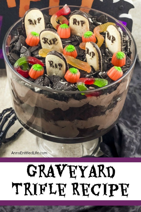 A layered chocolate trifle with a graveyard setting at the top (grave markers, pumpkins, gummy spiders, and crushed Oreos) in a clear trifle bowl, on top of a black and white table covering. A bone hand is on the left of the trifle bowl.