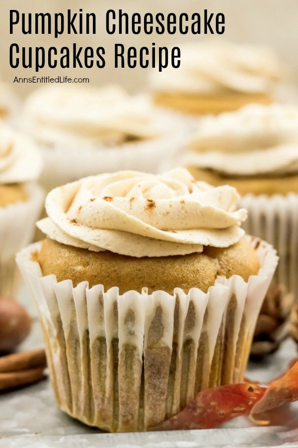 A close-up of a frosted pumpkin cheesecake cupcake sitting on an aluminum tray, a few faux fall foliage pieces are staged in front.