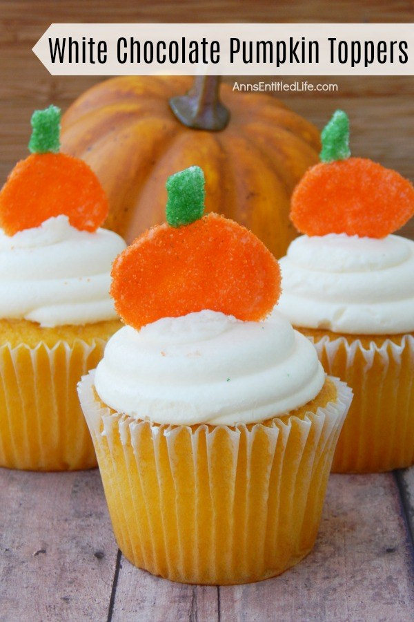 Close-up of three white cupcakes with white frosting and a pumpkin topper stuck in the frosting are set on a blue board. There is a faux pumpkin in the background.
