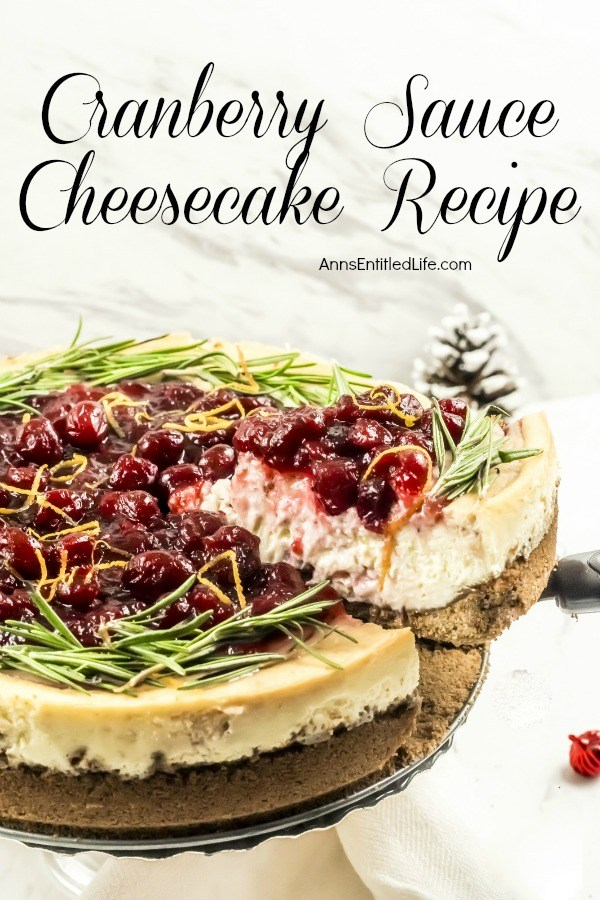 A serving of cranberry sauce topped cheesecake is being lifted from the whole cheesecake with a pie server. There is a pinecone in the upper left, a small red ornament in the lower right.