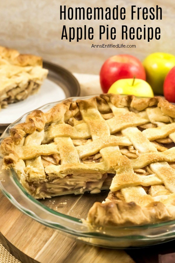 A homemade apple pie with a lattice top, one of the  pieces is removed and on a plate in the upper left. There are 3 fresh apples behind the pie. All this sits on a wooden board.
