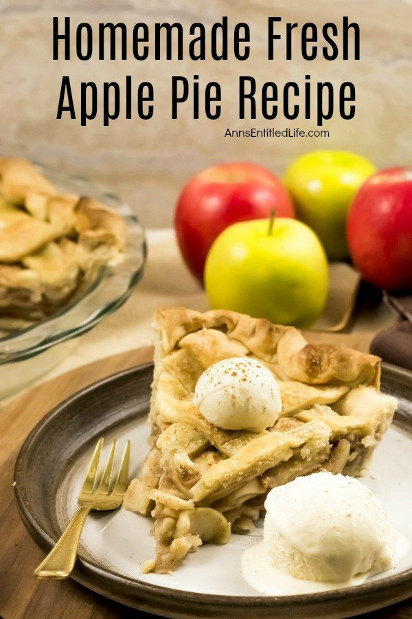 A homemade apple pie with a lattice top with one piece removed sits in the upper left. The plated pie of apple pie is served with a scoop of vanilla ice cream and sits on a dark plate. There are 3 fresh apples behind the pie. All this sits on a wooden board.