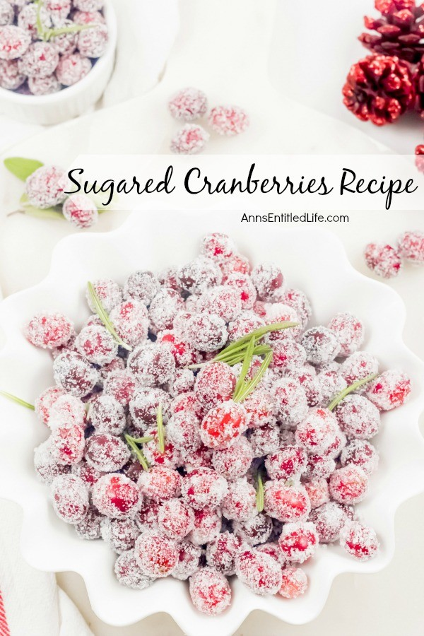 An overhead shot of a white bowl full of sugared cranberries (accented with rosemary). a smaller white bowl full in the upper left, red-colored pinecones in the upper right. All on a white background.