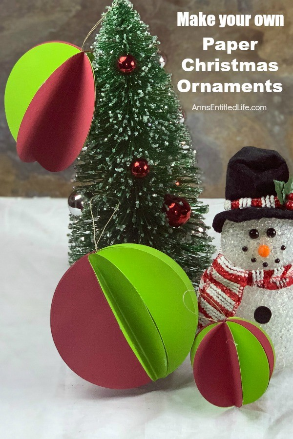 Three small green and red paper ornaments on a small evergreen tree. There is a faux snowman standing next to it.