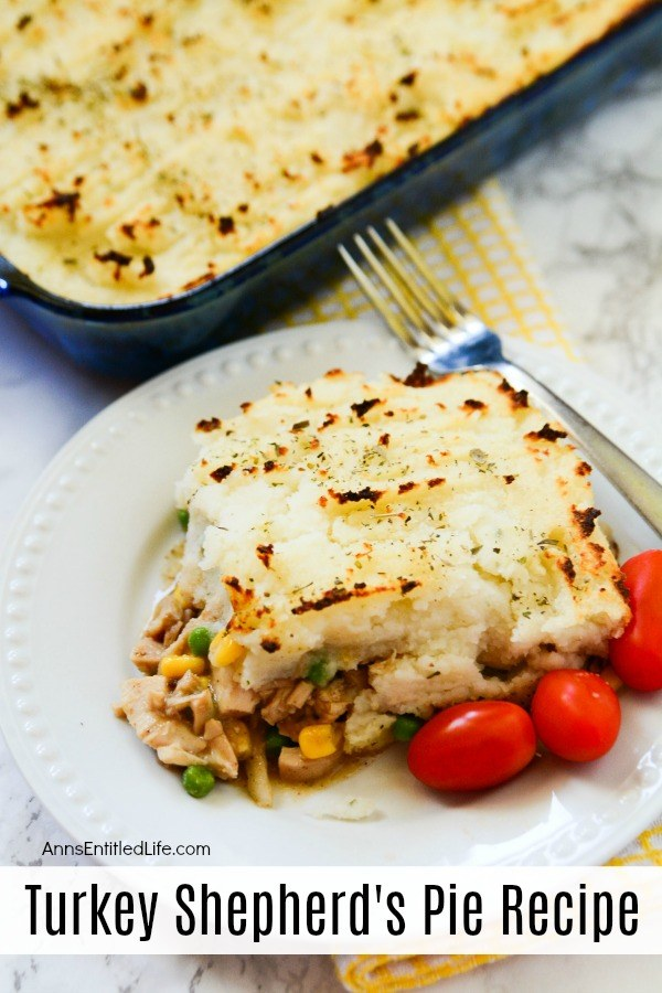 A serving of turkey Shepard pie on a white plate with a fork diagonally across the top of the plate, several tomatoes are garnish at the bottom of the plate. The remaining pie is in a pan in the upper left. A yellow checked dishtowel rests underneath the baking pan.