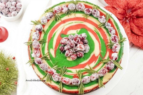 Christmas Cheesecake Recipe. Impress your friends and family with this gorgeous Christmas Cheesecake. You will delight taste buds when you serve this dressed-up classic sour cream cheesecake recipe for the holidays. The wonderful swirls of color add a dash of magical wonder to match the holiday season and form a perfect holiday dessert.
