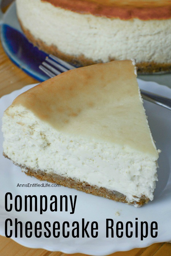 A slice of comany cheesecake site front and center on a white plate. The remaining cheesecake is underneath on a blue earthenwear dish in the background. This sits brown sideboard.