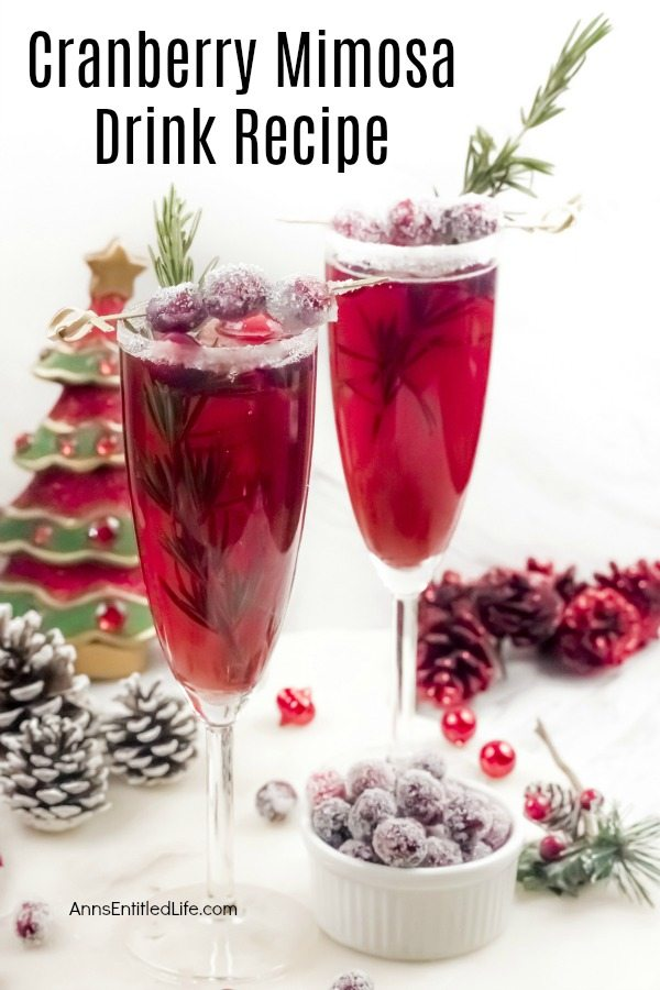 Two champagne flutes filled with cranberry mimosas, there is a white sugared rim, and garnished with rosemary inside the glass, and sugared cranberries on a stick on top. A white bowl filled with sugared cranberries sits at the bottom of the right flute, there is holiday decor on the white cupboard, and a faux Christmas tree in the back.