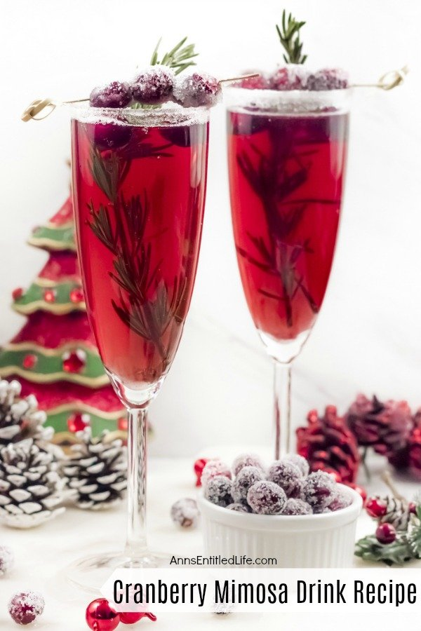 A close-up of two champagne flutes filled with cranberry mimosas, there is a white sugared rim, and garnished with rosemary inside the glass, and sugared cranberries on a stick on top. A white bowl filled with sugared cranberries sits at the bottom of the right flute, there is holiday decor on the white cupboard, and a faux Christmas tree in the back.