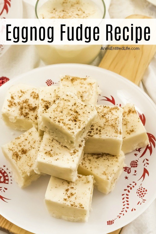 A white and red plate filled with cut pieces of eggnog fudge. There is a glass of eggnog directly above. They are sitting on a cutting board.