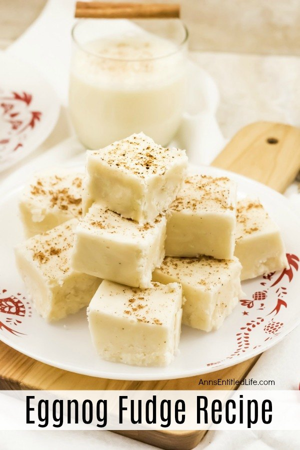 A white and red plate filled with cut pieces of eggnog fudge. There is a glass of eggnog directly above with a stick of cinnamon resting on the rim. They are sitting on a cutting board.