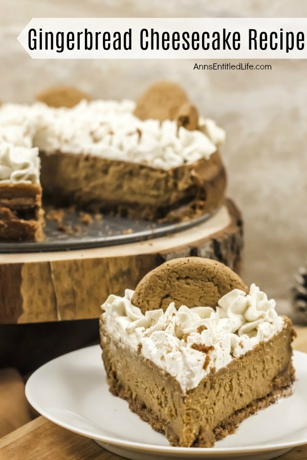 A front profiled slice of gingerbread cheesecake sits on a white plate. The rest of the cheesecake sits on top of a wooden serving tray in the upper left of the photo.
