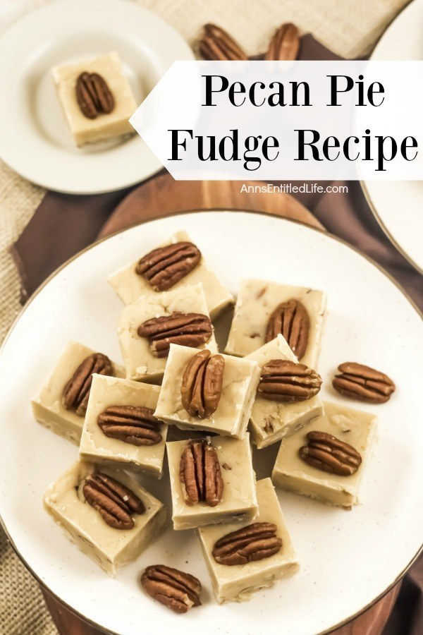 An overhead view of a white plate with gold trim that is filled with stacked pieces of pecan pie fudge. In the background is a second plate of fudge in the upper right, a few pecan halves sit in the center back, and to the back left is a plate with a single piece of pumpkin pie fudge.
