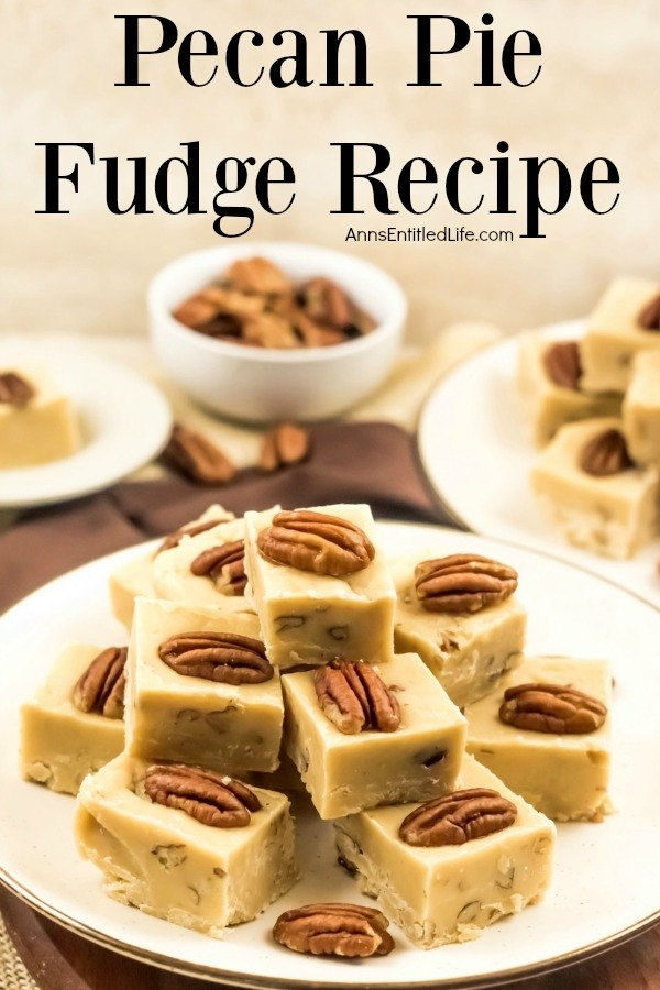 A white plate with gold trim is filled with stacked pieces of pecan pie fudge. In the background is a second plate of fudge in the upper right, a bowl of chopped pecan sits in the center back, and to the back left is a plate with a single piece of pumpkin pie fudge.