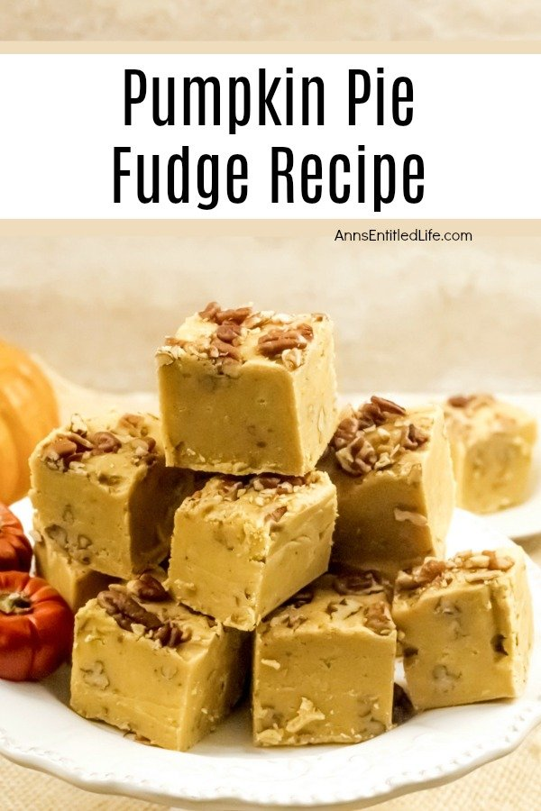 A stack of cut pumpkin pie fudge sitting on on a white plate is front and center. Several decorative faux orange pumpkins are sitting on the left side of the plate.