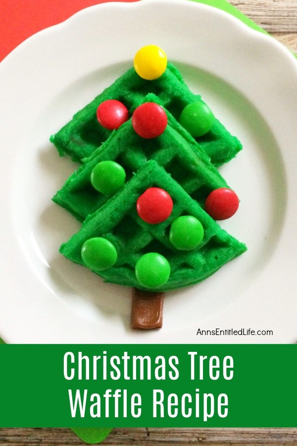Green colored waffle in the shape of a Christmas tree on a white plate