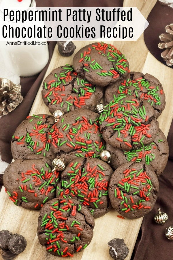 An overhead view of a cutting board filled with peppermint patty chocolate cookies. There are small gold ornaments decorating the pile. There is a glass of milk in the upper left, and peppermint patty cookies decorating the area.