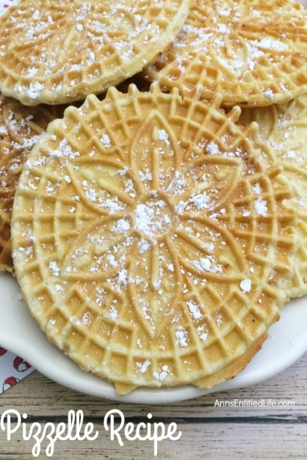 An upclose view of a white plate filled with pizzelles which are covered in powder sugar.
