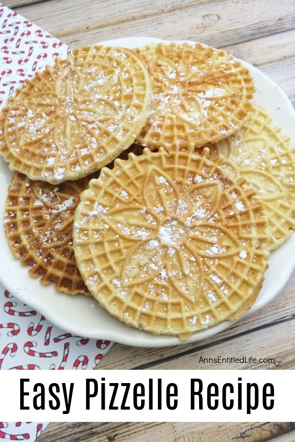 A white plate filled with pizzelles which are covered in powder sugar
