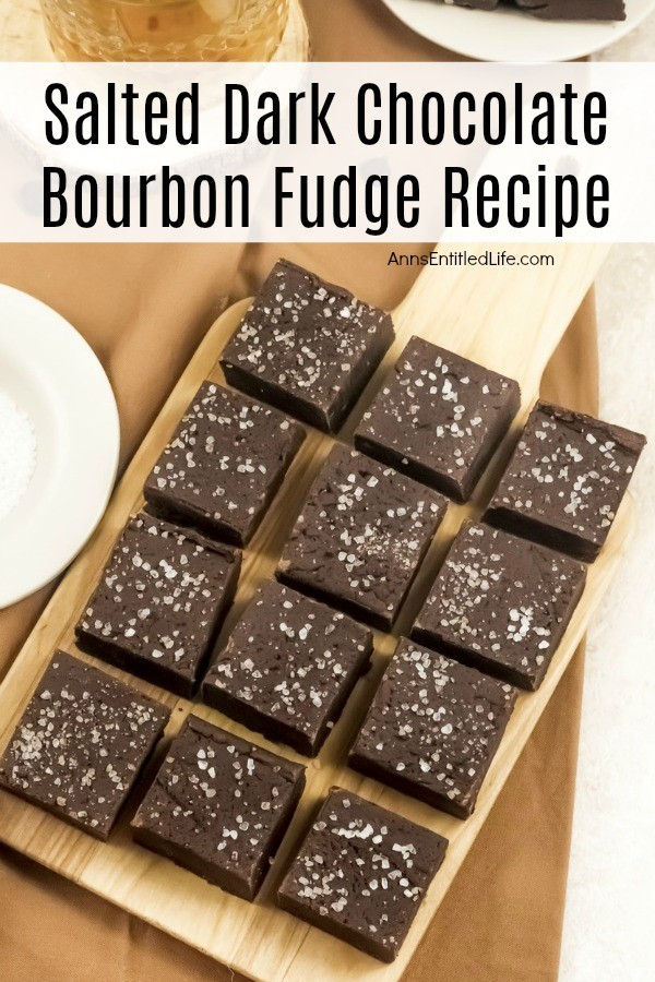 An overhead view of 12 square pieces of salted dark chocolate bourbon fudge on a wooden cutting board which is set upon a gold napkin. There are three plates surrounding the cutting board on the outer edges of the image.