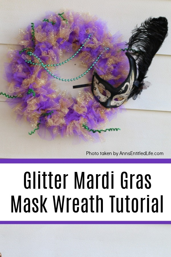 glittery purple, green, and gold Mardi Gras wreath with a black mask on the right, hanging on a hook