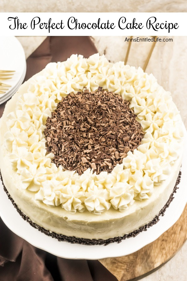 An overhead view of a white frosted cake trimmed with ruffle mounds, and chocolate shavings in the middle, on a white cake plate. There is a small stack of white-colored plates and some gold silverware in the upper left.