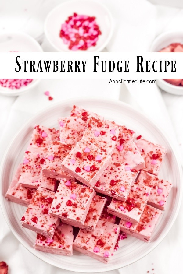 An overhead view of strawberry fudge squares stacked in a pyramid shape on a white plate. There are small bowls of red sprinkles that surround the plate.