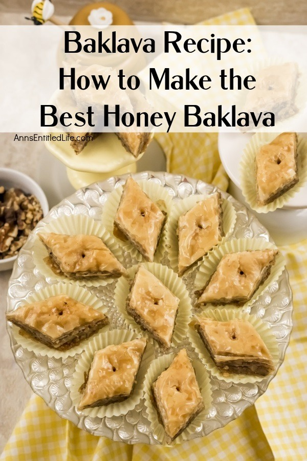 Overhead view of diamond-shaped baklava in white paper holders on a clear pastry dish, more pieces are in plates above, a honey pot is in the top left, and to the immediate left is a white plate of shelled walnuts