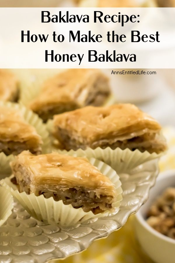 A close up view of diamond-shaped baklava in white paper holders on a clear pastry dish.