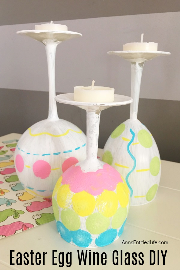 Three wine glasses painted to resemble Easter eggs sitting on a bunny matt.