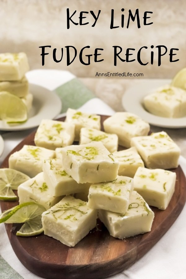 A wooden tray filled with cut squares of key lime fudge, garnished with limes. In the background are white bowls filled with more fudge