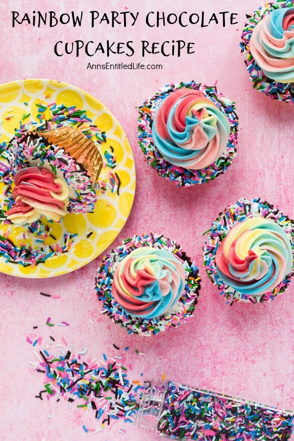 4 rainbow party chocolate cupcakes on the right hand side, a yellow plate is to the left with one tipped cupcake, a container of colored sprinkles is tipped over down below. All is set on a pink background.