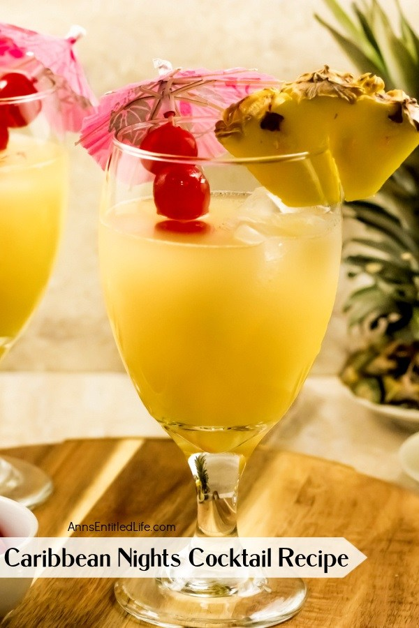 close-up of a Caribbean Nights cocktail, garnished with pineapple and cherries and cocktail umbrella
