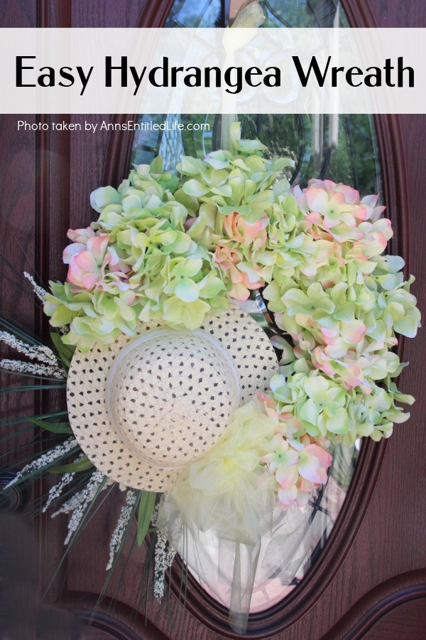 Up close photo of a Hydrangea Wreath made with a hat, hanging off a door hanger against a brown door with a glass window.