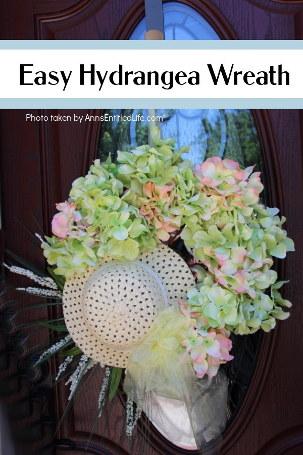 A left side photo of a Hydrangea Wreath made with a hat, hanging off a door hanger against a brown door with a glass window.