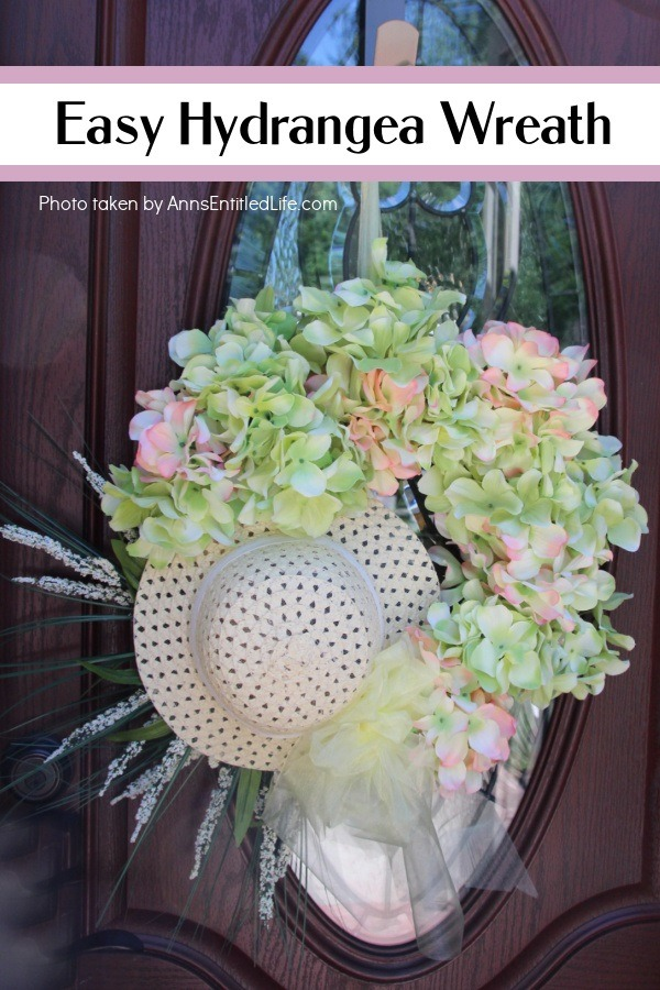 a photo of a Hydrangea Wreath made with a hat, hanging off a door hanger against a brown door with a glass window.