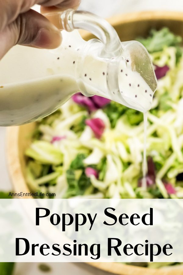 A close-up of a female hand pouring poppy seed dressing from a cruet into a salad below