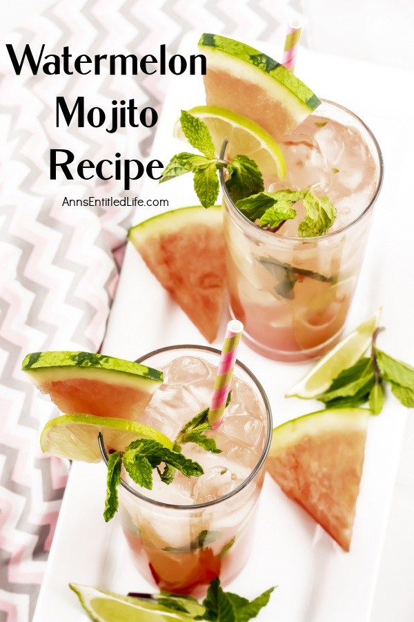 Overhead view of two watermelon mojitos on a white tray surrounded by cut watermelon, lime slices, and min springs. This sits on a pink and grey chevron napkin.