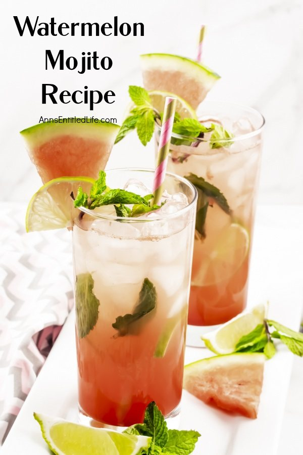 Two watermelon mojitos on a white tray surrounded by cut watermelon, lime slices, and min springs. This sits on a pink and grey chevron napkin.