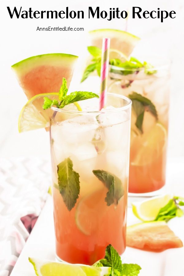 Two watermelon mojitos, one cocktail is front and center, on a white tray surrounded by cut watermelon, lime slices, and min springs. This sits on a pink and grey chevron napkin.