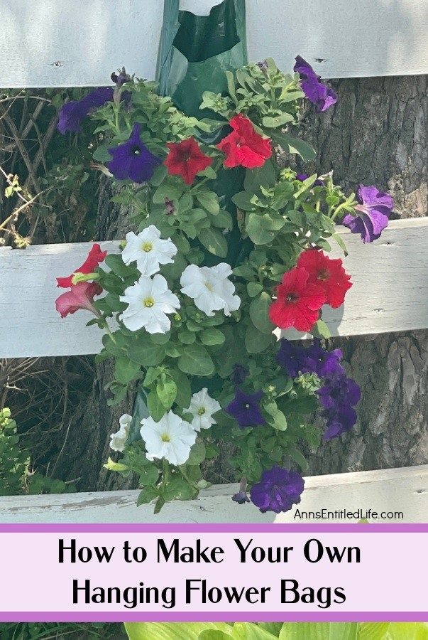 a hanging flower pouch filled with red, white, and purple petunias hanging on a white fence with a tree trunk in the background