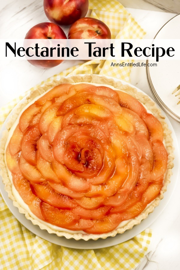 Overhead view of a nectarine tart on a white and yellow checked cloth. There are fresh nectarines above the tart, and a partial view of white plates on the right.