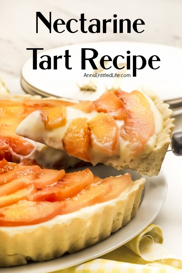 A piece of a nectarine tart is being lifted from the tart below. There are white plates and gold forks above the tart.