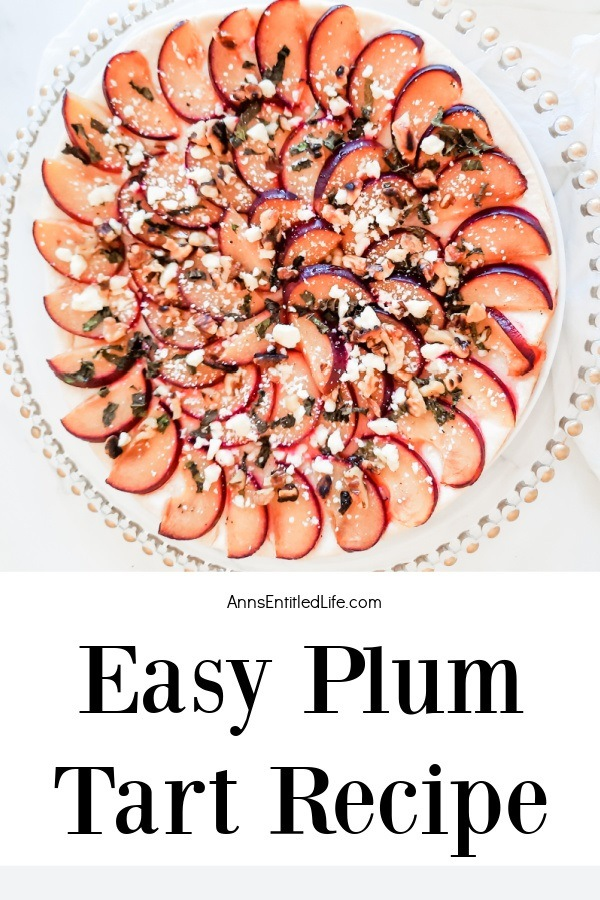 A whole plum tart is sitting on a clear dish